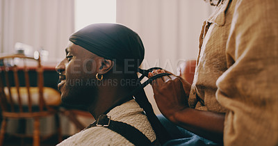 Buy stock photo Shot of a young woman tying a hair wrap on her husband in the living room at home