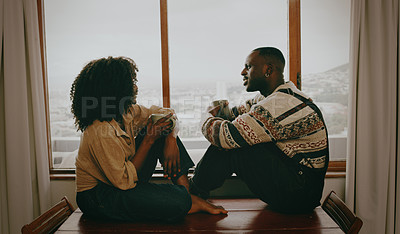 Buy stock photo Shot of a young couple having coffee and a chat at home