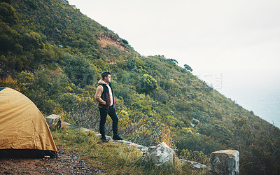 Buy stock photo Shot of a young man admiring the view while camping on a mountain