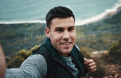 Buy stock photo Shot of a young man taking selfies while out on a hike