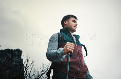 Buy stock photo Shot of a young man using a walking pole while out on a hike
