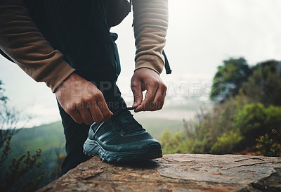 Buy stock photo Closeup shot of an unrecognisable man tying his laces while out on a hike
