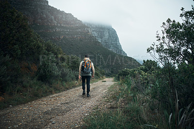 Buy stock photo Rearview shot of a young man hiking through the mountains