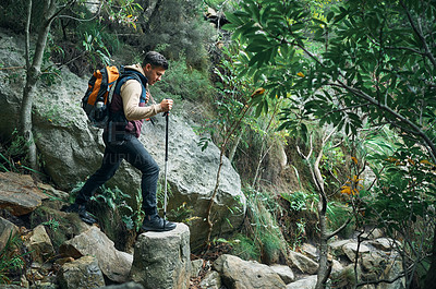 Buy stock photo Shot of a young man using a walking pole while hiking through the mountains