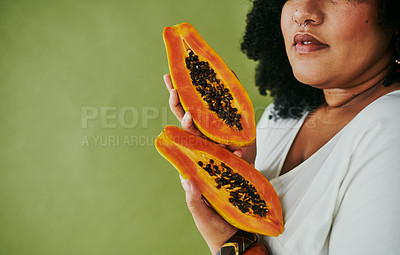 Buy stock photo Studio shot of a woman holding papaya against a green background