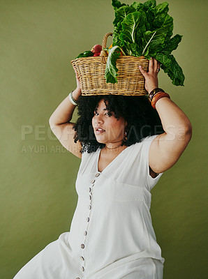 Buy stock photo Studio shot of a woman holding a basket of fresh vegetables against a green background