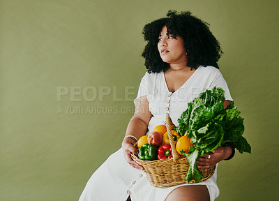 Buy stock photo Studio shot of a young woman holding a basket of fresh fruit and vegetables against a green background