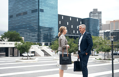Buy stock photo Shot of two mature businesspeople having a discussion while standing in the city