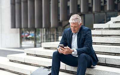 Buy stock photo Shot of a mature businessman using a cellphone while sitting on a staircase in the city