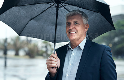 Buy stock photo Shot of a mature businessman holding an umbrella while out in the city