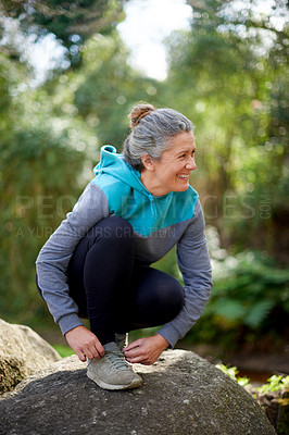 Buy stock photo Shot of a mature woman tying her shoelaces before a jog out in nature