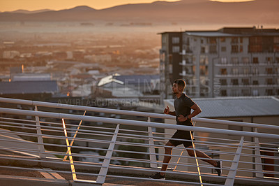 Buy stock photo Shot of a sporty young man running on a bridge in the city