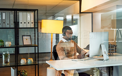 Buy stock photo Shot of a young businessman wearing a headset and while going through paperwork in an office at night