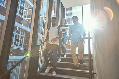 Buy stock photo Shot of a group of young businesspeople walking downstairs in a modern office