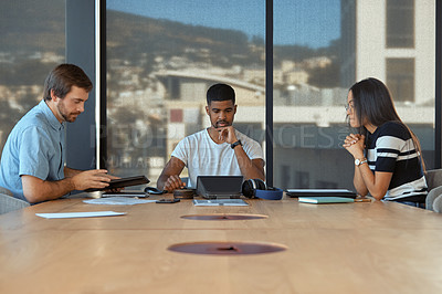 Buy stock photo Shot of a group of young businesspeople using a conference phone during a meeting in a modern office