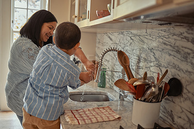 Buy stock photo Shot of a young boy helping his mother with the dishes at home