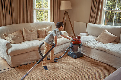 Buy stock photo Shot of an adorable little boy vacuuming the living room carpet