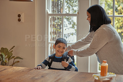 Buy stock photo Shot of a mother getting her young son ready for school