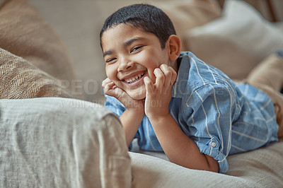 Buy stock photo Shot of an adorable little boy lying on the couch at home