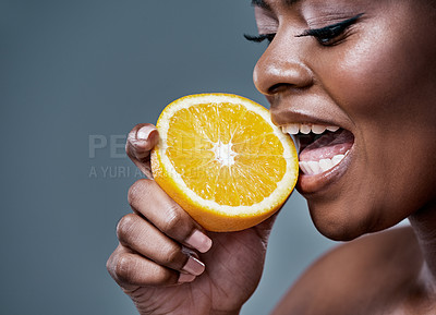 Buy stock photo Cropped shot of a beautiful young woman biting into an orange