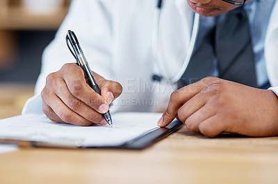 Buy stock photo Closeup shot of an unrecognisable doctor writing notes on a clipboard in an office