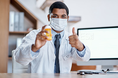 Buy stock photo Portrait of a young doctor holding a bottle of pills and showing thumbs up in his office