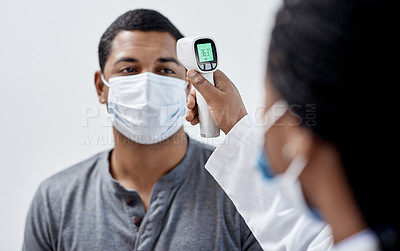 Buy stock photo Shot of a young man getting his temperature taken with an infrared thermometer by a doctor