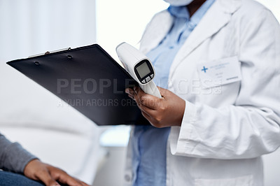 Buy stock photo Closeup shot of an unrecognisable doctor writing notes and holding an infrared thermometer during a consultation with a patient