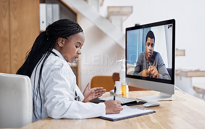 Buy stock photo Shot of a young doctor writing notes during a video call with a patient on a computer