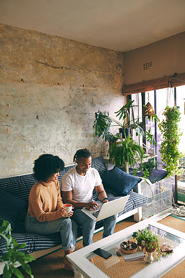 Buy stock photo Shot of a young couple using a laptop together at home