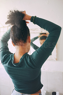 Buy stock photo Rearview shot of a young woman tying her hair in the bathroom at home