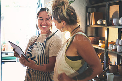 Buy stock photo Shot of two young women using a digital tablet while working together in a pottery studio