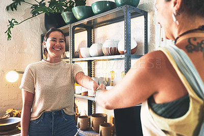 Buy stock photo Shot of two young women shaking hands in a pottery studio