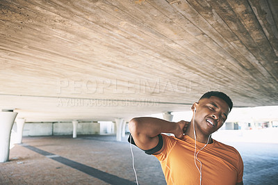 Buy stock photo Shot of a young man experiencing neck pain while working out against an urban background