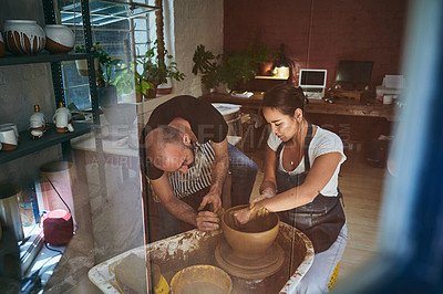Buy stock photo Shot of a young man and woman working with clay in a pottery studio