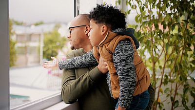 Buy stock photo Shot of an adorable little boy looking out of a window at home with his father