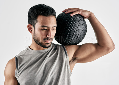 Buy stock photo Studio shot of a muscular young man holding an exercise ball against a white background