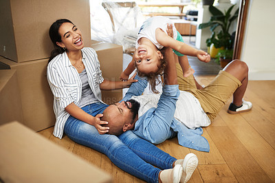 Buy stock photo Shot of a young family of three relaxing on the floor of their new home beside moving boxes while the father lifts his toddler up in the air
