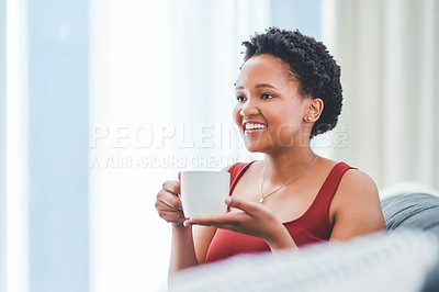 Buy stock photo Cropped shot of a young lady smiling while enjoying a cup of tea on the couch in her apartment