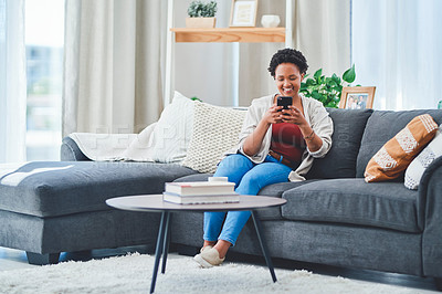Buy stock photo Shot of a young lady using her mobile phone and smiling while sitting on her couch in her apartment