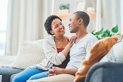 Buy stock photo Cropped shot of a loving young couple sitting together on the couch in their apartment while she rests her hands on his shoulder
