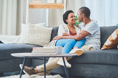Buy stock photo Shot of a young loving couple looking endearingly at each other while she has her legs across his waist sitting on the couch in their apartment