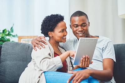 Buy stock photo Cropped shot of a smiling young loving couple browsing on a tablet together while she has her legs across his waist sitting on the couch in their apartment