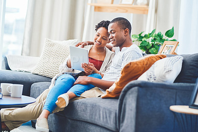 Buy stock photo Shot of a young loving couple browsing on a tablet together while she has her legs across his waist sitting on the couch in their apartment