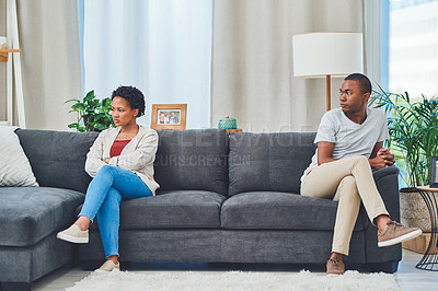 Buy stock photo Shot of a young couple sitting apart on a couch after an argument while he looks at her in disdain