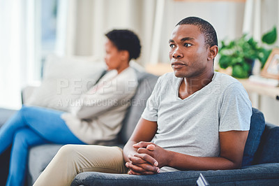 Buy stock photo Cropped shot of a young couple sitting apart on a couch after an argument while he looks away from her