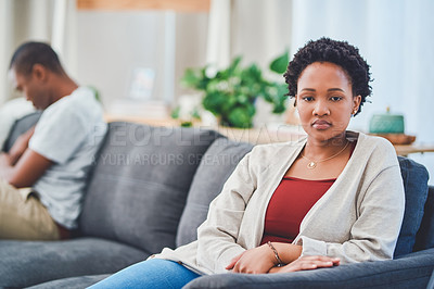 Buy stock photo Cropped shot of a young couple sitting apart on a couch after an argument while she looks away from her
