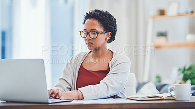 Buy stock photo Cropped shot of a young lady typing on her laptop while working from home at her desk