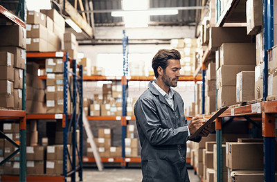 Buy stock photo Shot of a young man using a clipboard while working in a warehouse