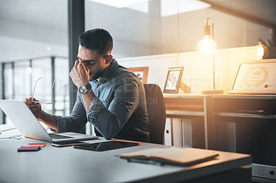 Buy stock photo Cropped shot of a handsome young businessman suffering from a headache during a late shift in the office